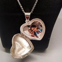 Load image into Gallery viewer, Large silver heart shaped photo locket on silver chain displayed on a black bust. Locket is open showing photo of two little girls inside.