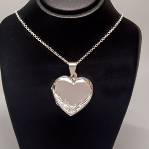 Large silver heart shaped photo locket on silver chain displayed on a black bust.