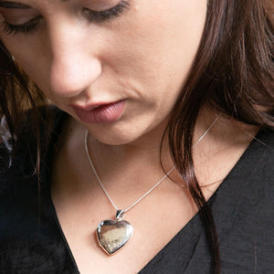 Model wearing black top looking downwards with eyes. Model is wearing silver heart shaped photo locket with a silver Italian chain.
