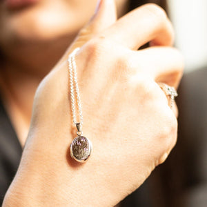Girl's hand displaying oval silver photo locket necklace with Italian silver chain.