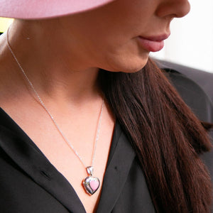 Female model wearing pink hat and black shirt and silver heart shaped photo locket with pink mother of pearl inset.t