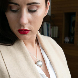 Model wearing beige coat and white shirt and silver clam shell photo locket. Model is looking downwards.