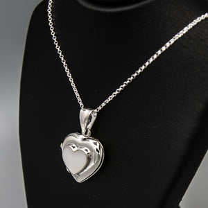 Silver heart shaped photo locket with white mother of pearl inset with a silver Italian chain displayed on a black bust.