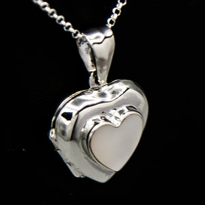 Silver heart shaped photo locket pendant with white mother of pearl inset with a silver Italian chain displayed on a black bust.