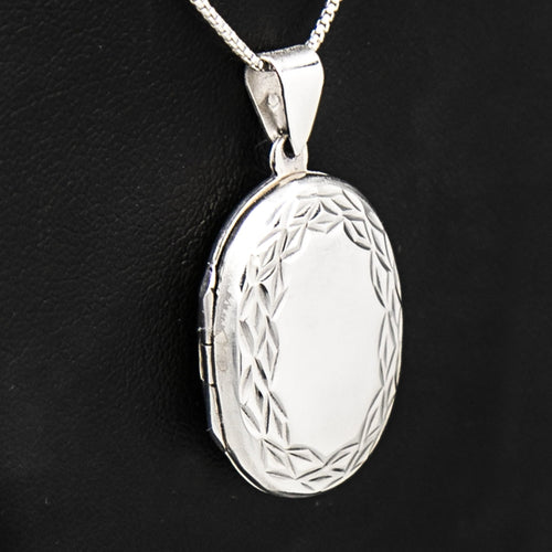 Large Oval shaped silver photo locket on italian silver chain, displayed on black bust.