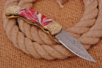 CUSTOM HAND FORGED DAMASCUS STEEL FOLDING KNIFE WITH RED RISEN HANDLE AND ENGRAVED BRASS BOLSTER  AH-1052