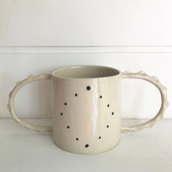 Hand thrown white ceramic two handled mug decorated with little black spots