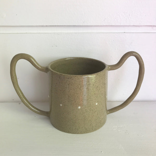 Hand thrown buff coloured ceramic mug decorated with little white spots