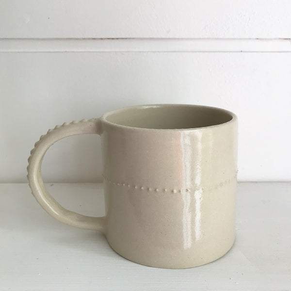 Hand thrown white ceramic mug decorated with raised white spots