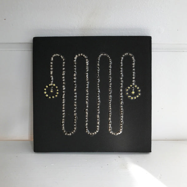 black ceramic tile with white and yellow slip decoration