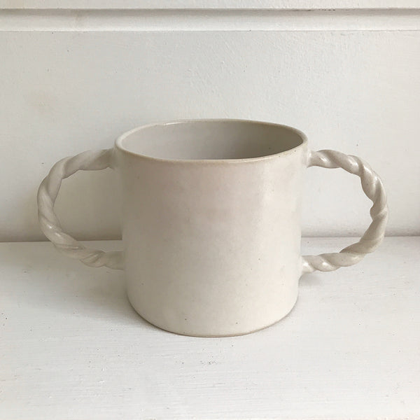 Hand thrown white ceramic two rope twist handled mug decorated with little raised white spots