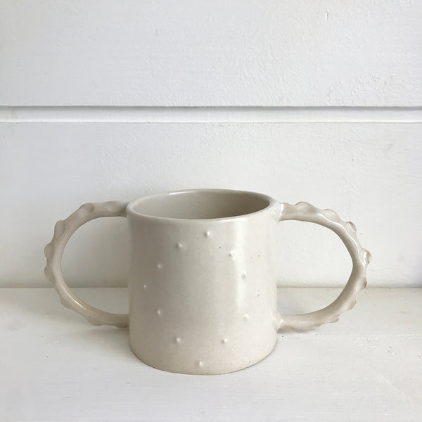Hand thrown white ceramic two handled mug decorated with little raised white spots