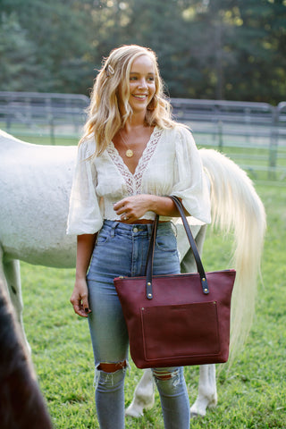 woman in jeans and blouse stands in a pasture by the flank of a horse holding a merlot leather tote