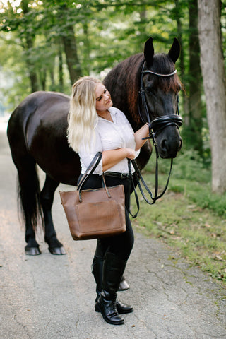 woman in shirt and riding pants stands by the head of a black horse holding a mocha leather tote