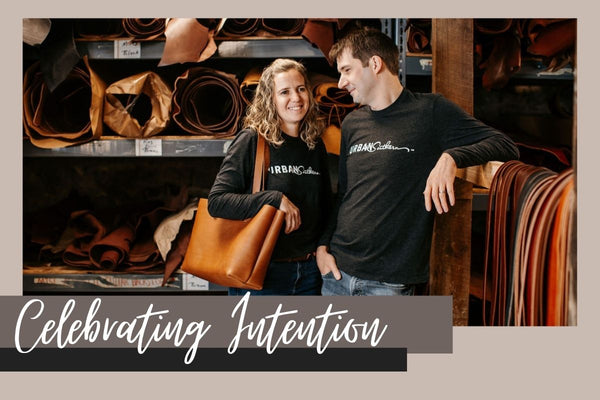 """Rachel and Daniel Smucker stand in front of shelves filled with leather. Daniel is looking at Rachel and smiling. White script reads """"Celebrating Intention"""""""
