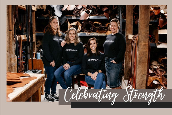 """4 women stand together smiling in a shop surrounded by rolls of leather, white script reads """"Celebrating Strength"""""""