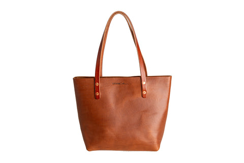 cognac leather tote bag floating on a white background