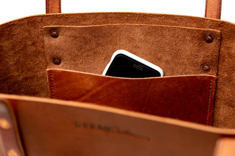 Close up of opening of a leather tote bag showing an interior pocket with a cell phone peeking out