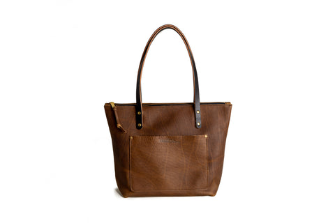 mocha leather tote bag with black handles and an exterior front pocket on white background