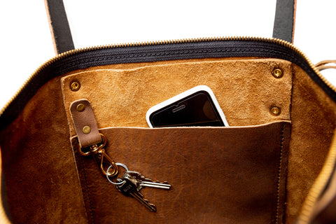close up of interior of mocha leather tote showing pocket & key fob with cell phone peeking out