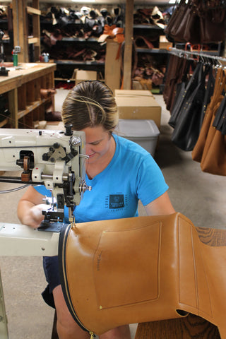 same woman sits at industrial sewing machine making a leather tote bag