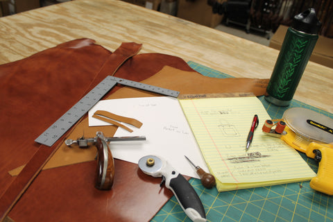 overhead shot of a work table with leather tools and a note pad