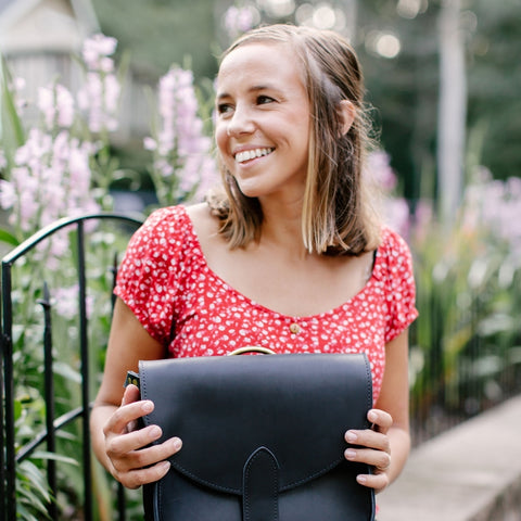 smiling girl in red blouse holds black leather bag in lap as she sits on a low stone wall