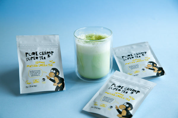 lemon matcha latte next to purechimp lemon matcha pouches and on a baby blue background