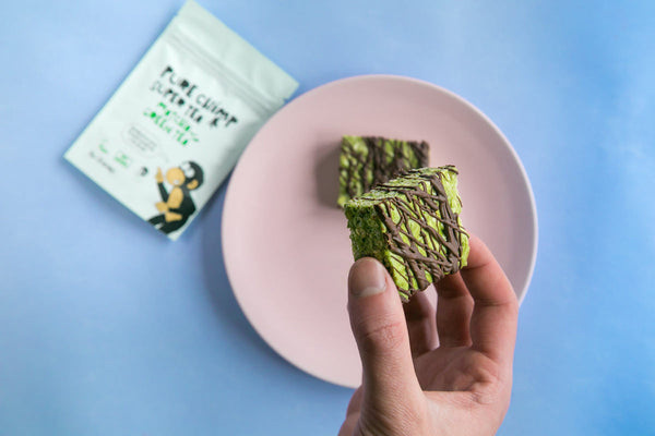 matcha marshmallow krispie squares in hand