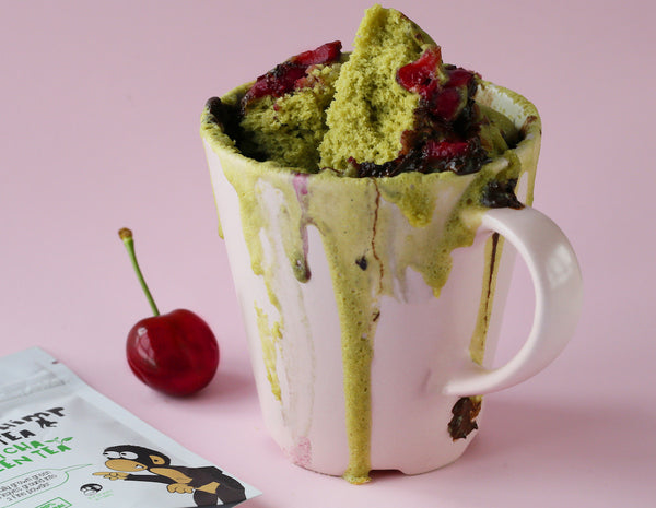 green matcha mug cake in a white cup and cut in half with cherries oozing out