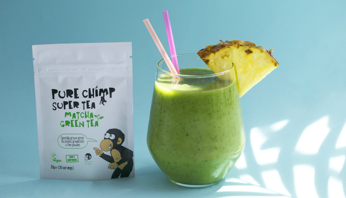 ready to drink matcha pineapple smoothie next to a pouch of regular purechimp matcha