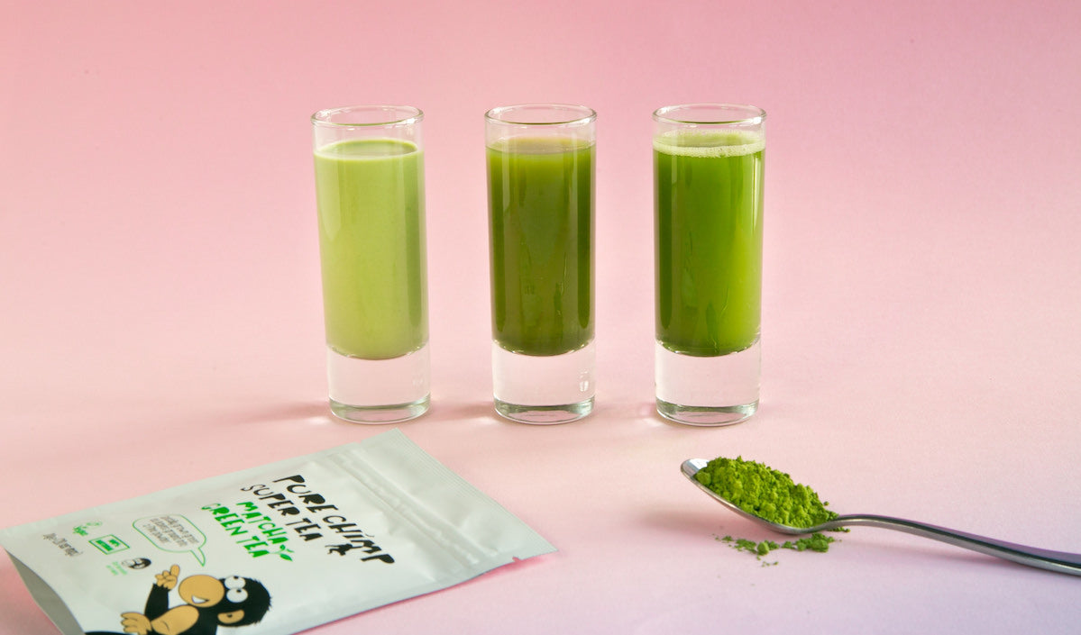 matcha shots on a pink background with loose vibrant green matcha on a spoon