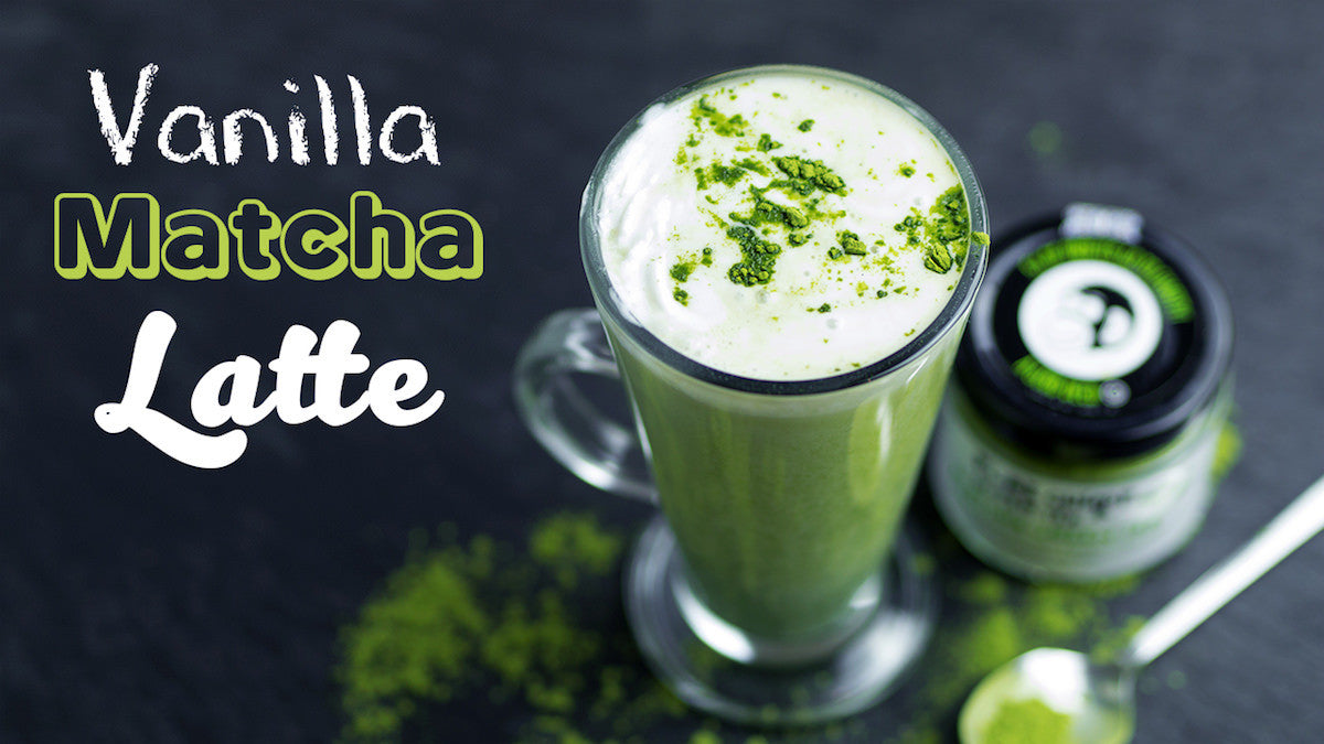 Vanilla Matcha Latte in a clear glass mug with cream and matcha sprinkles