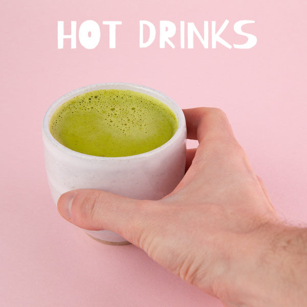 matcha green tea latte with white text stating hot drinks