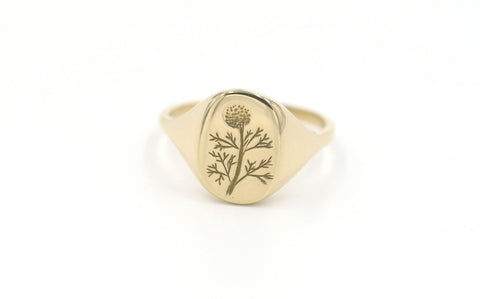 Yellow gold signet ring by Erin Claus with dandelion engraving