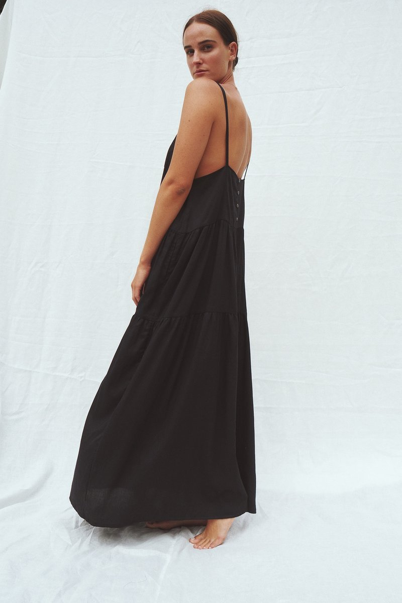 Model wearing the Austen tiered maxi dress in black - UNIK by us - side view