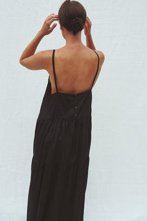 Model wearing the Austen tiered maxi dress in black - UNIK by us - back view