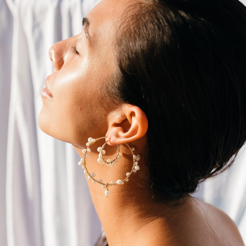 Model wearing the Tom Large Earrings - 14k gold-filled hoop earrings with a 5cm diameter and string of freshwater pearls, by Elvis et moi