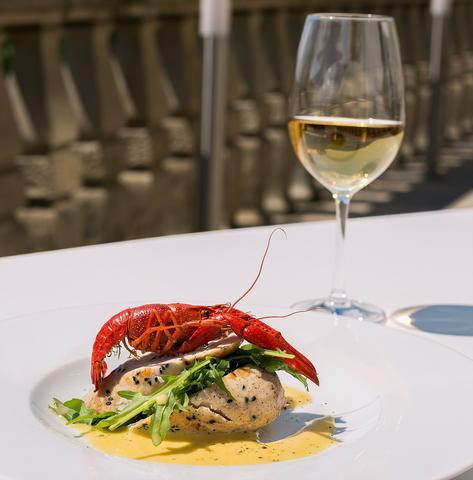 image of lobster with a glass of white wine at white table setting