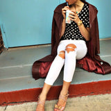 woman on steps with white jeans and polkadot shirt sipping drink wearing a gold dragon with tail cuff