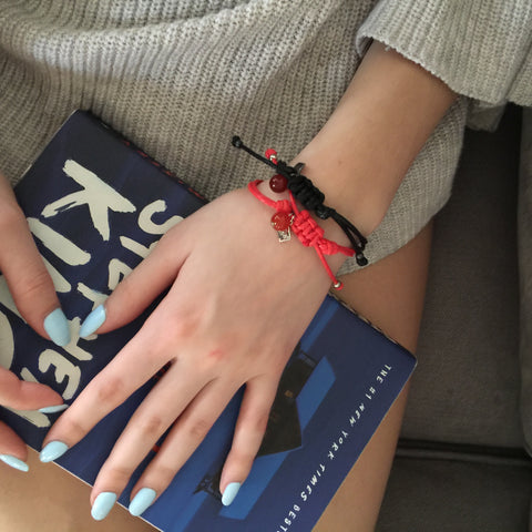 Friendship Bracelet - String of Destiny in Red and Black on lap with a book