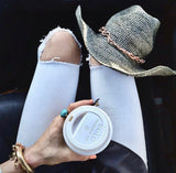 view point looking down on a woman with ripped jeans and cowboy hat on knees holding a coffee wearing dragon with tail cuff