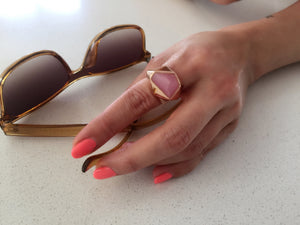 Hand wearing Lattice Cocktail Ring on hand on white table with sunglasses