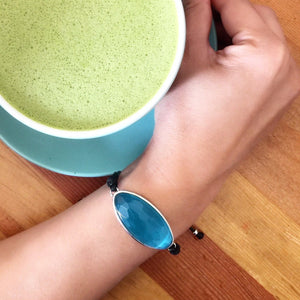 blue inclusiveness  Bracelet - Dress For Success Vancouver | Values Bracelet on wrist next to a blue cup with matcha