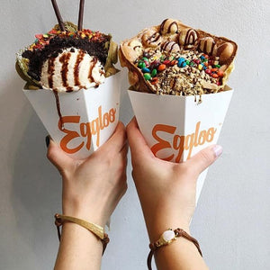 two girls with arm up holding up waffle ice cream cones wearing Dagger and Buddha Corded Bracelet With Druzy