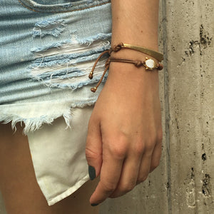 girl in cut off denim with hand on the side wearing Mantra Dagger Corded Bracelet and Buddha Corded Bracelet