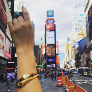 girl in Times Square holding up her hand wearing Mantra Dagger Corded Bracelet and Buddha Corded Bracelet