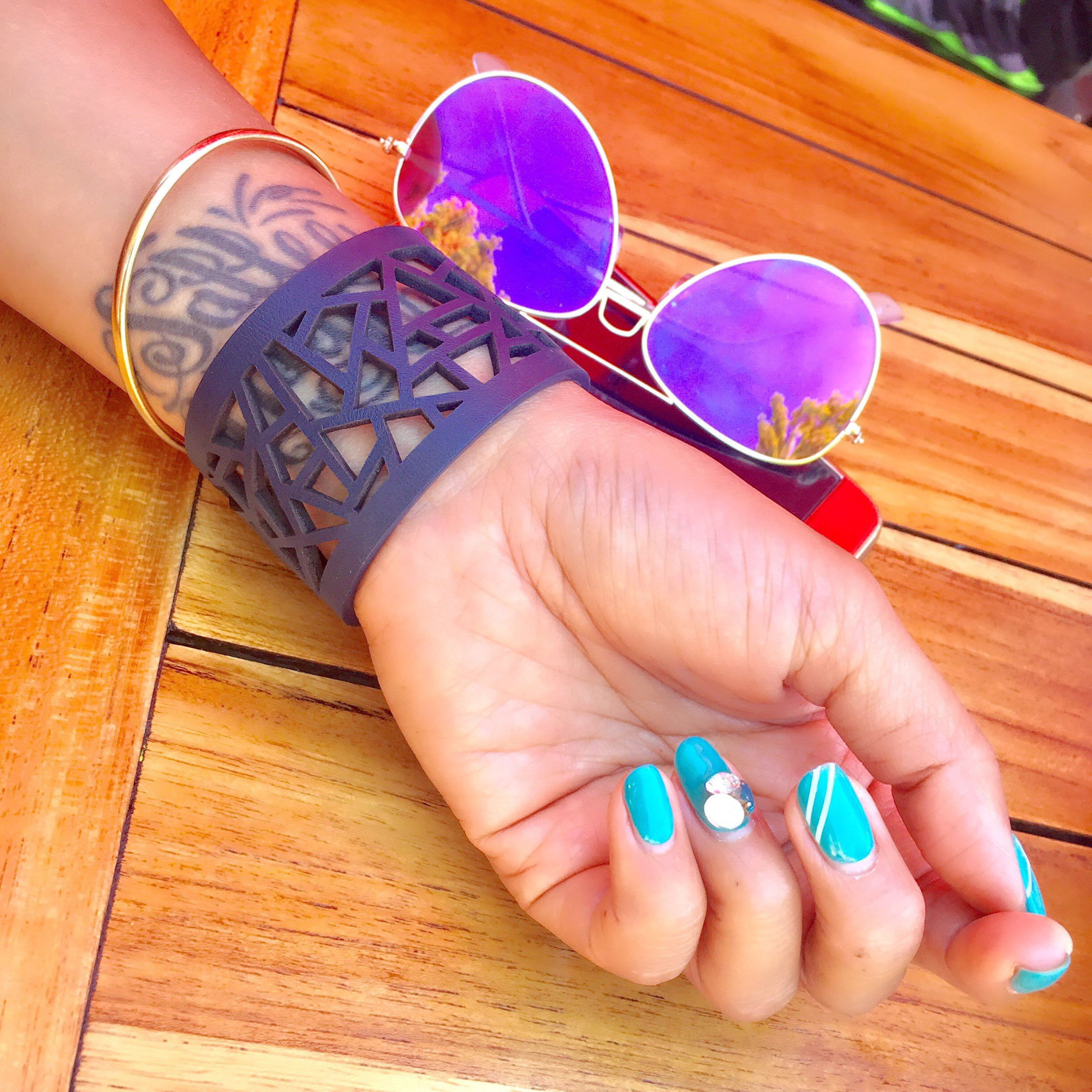 Blue manicured hand with tattoo against a table next to sunglasses wearing Margaret - Lattice Leather Laser Cut Bracelet