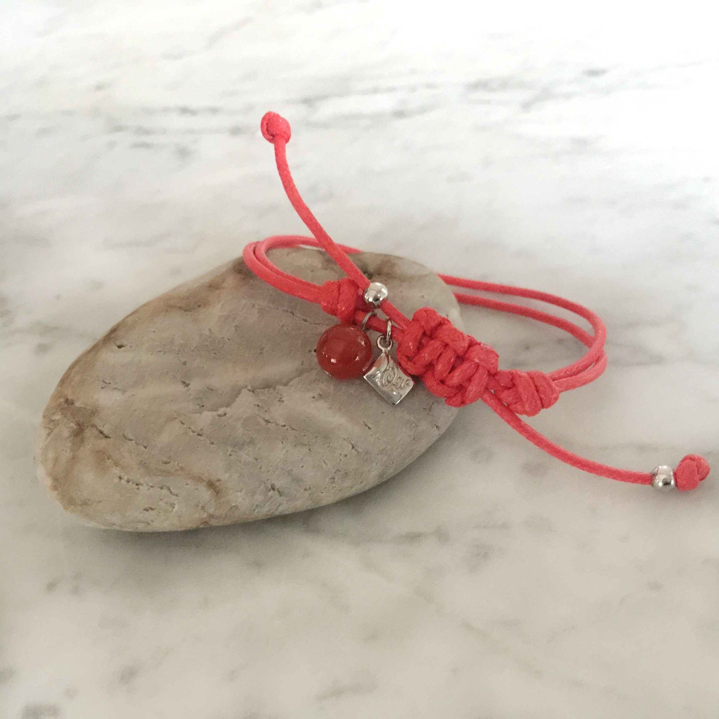 Red strings of destiny bracelets With Red Carnelian Bracelet on rock