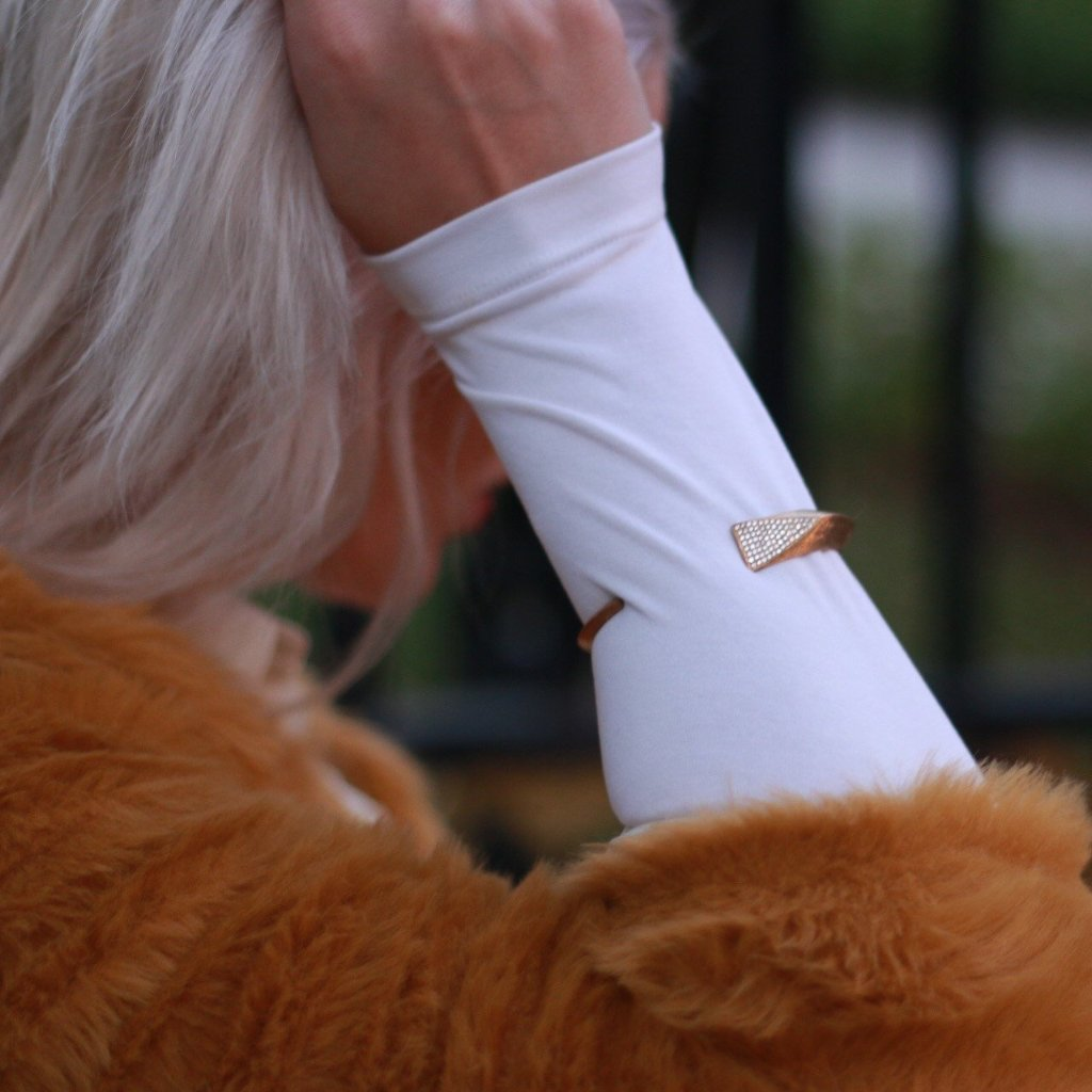 platinum blond wearing fur and white shirt wearing Mantra Dagger Corded Bracelet - gold, swarovski crystals